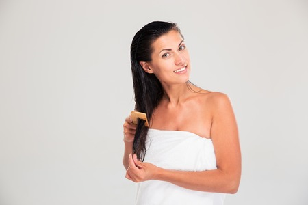 comb hair: Portrait of a happy woman combing her hair isolated on a white background. Looking at camera Stock Photo
