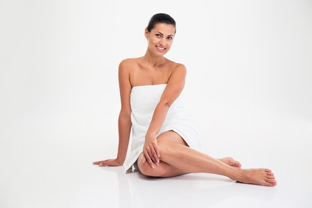 womanliness: Portrait of a smiling attractive woman in towel sitting on the floor isolated on a white background. Looking at camera Stock Photo