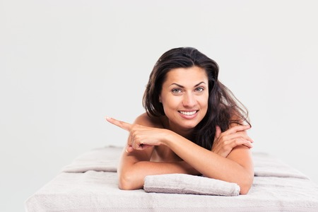 looking away from camera: Happy woman lying on massage lounger and pointing finger away. Looking at camera Stock Photo