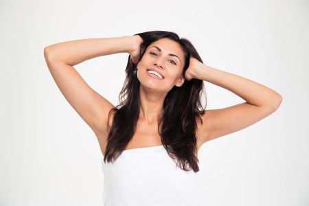 hair treatment: Portrait of a smiling woman in towel touching her hair and looking at camera isolated on a white background