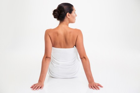 Back view portrait of a young woman in towel sitting on the floor isolated on a whtie background