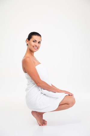 womanliness: Portrait of a smiling pretty woman in towel sitting on the floor isolated on a white background Stock Photo