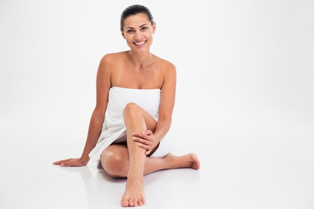 womanliness: Smiling cute woman in towel sitting on the floor isolated on a white background. Looking at camera
