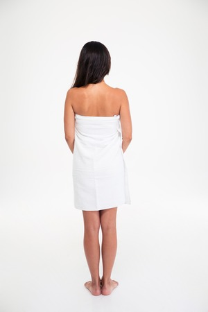 Back view portrait of a woman with fresh skin standing in towel isolated on a white background