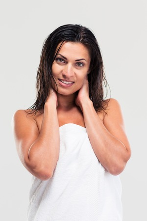 Portrait of a happy woman with towel and wet hair standing isolated on a white background photo