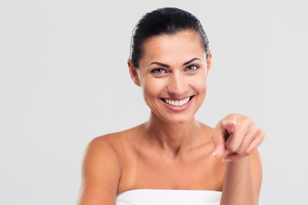 Portrait of a smiling woman in towel pointing finger at camera isolated on a white background photo