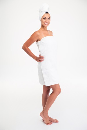 Full length portrait of a happy cute woman in towel standing after bath isolated on a white background photo