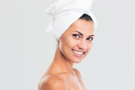 Beauty portrait of a smiling beautiful woman with fresh skin and towel on head looking at camera isolated on a white background photo