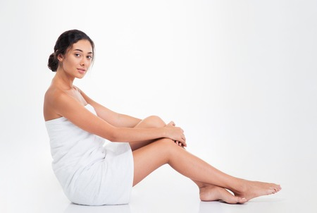 womanliness: Beautiful young woman in towel sitting on the floor isolated on a white background