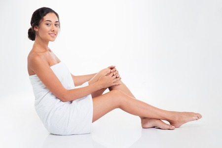 womanliness: Happy attractive woman in towel sitting on the floor isolated on a white background