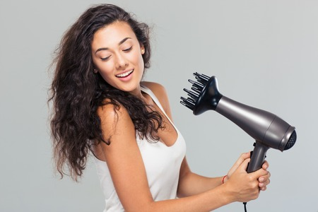 dryer: Portrait of a smiling young woman dries her hair over gray background Stock Photo