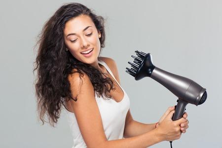 secador de pelo: Retrato de una mujer joven y sonriente se seca el pelo sobre fondo gris