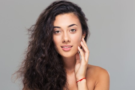 desnudo de mujer: Retrato de la belleza de una muchacha linda con la piel fresca mirando a la cámara sobre fondo gris Foto de archivo