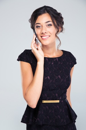 black dress: Smiling woman in black dress talking on the phone isolated on a white background and looking at camera Stock Photo