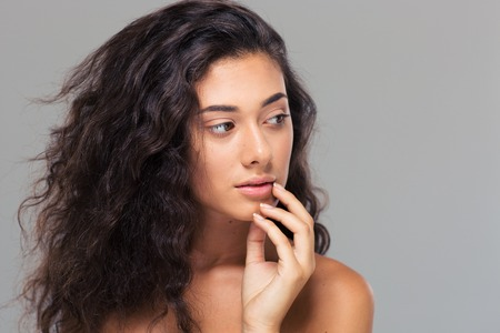 modelos desnudas: Retrato de la belleza de una mujer hermosa con la piel fresca que mira lejos sobre fondo gris