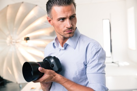 looking away from camera: Portrait of a confident photographer holding camera and looking away in studio