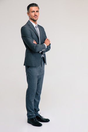 Volledige lengte portret van een zelfverzekerde zakenman stond met de armen over elkaar geïsoleerd op een witte achtergrond. kijken naar de camera