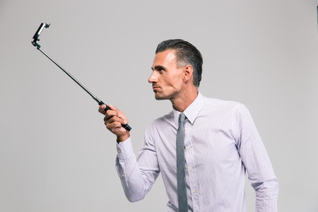 concetrated: Portrait of a handsome businessman holding selfie stick isolated on a white background