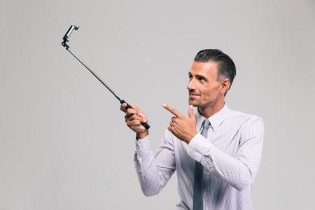 Ritratto di un bastone selfie bel uomo d'affari holding isolato su uno sfondo bianco Archivio Fotografico - 44601075