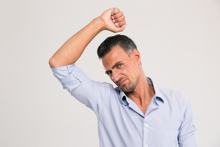 unbearable: Man smelling sniffing his armpit something smells bad foul odor isolated on a white background