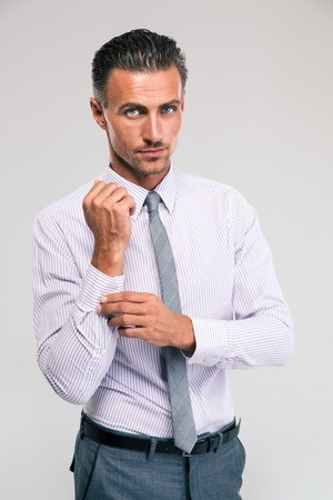 cuff: Handsome businessman buttoning cuff sleeves isolated on a white background