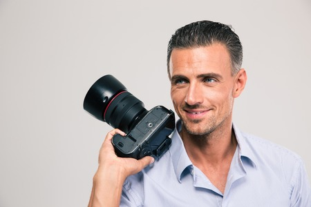 looking away from camera: Portrait of a smiling handsome man holding camera and looking away isolated on a white background Stock Photo