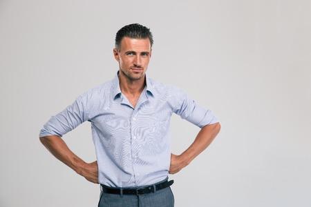 Portret van een knappe zakenman op een grijze achtergrond staan en naar de camera kijken Stockfoto