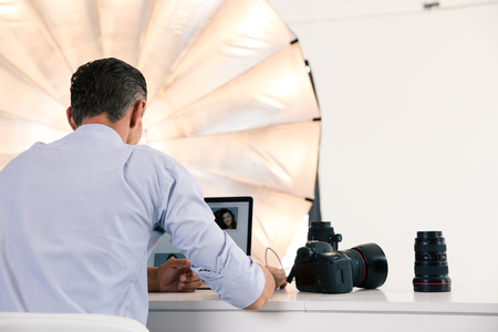 business owner: Back view portrait of photographer using laptop at his workplace