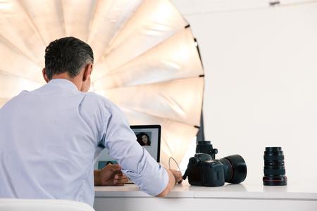 Terug portret van fotograaf met behulp van laptop op zijn werkplek