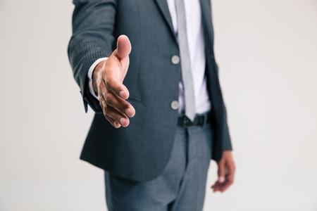 saludo de manos: Primer retrato de un hombre de negocios que estira la mano para apret�n de manos aislado en un fondo blanco