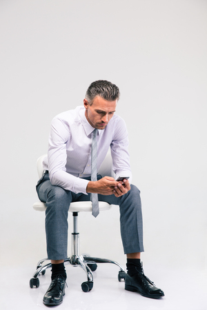 serious businessman: Portrait of a handsome businessman sitting on the office chair and using smartphone isolated on a white background Stock Photo