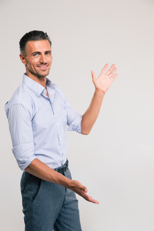 handsign: Businessman bragging about the size of something over gray background. Looking at camera