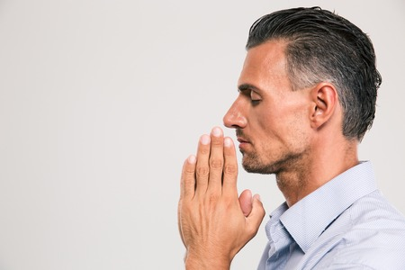 closed business: Side view portrait of a handsome man praying over gray background