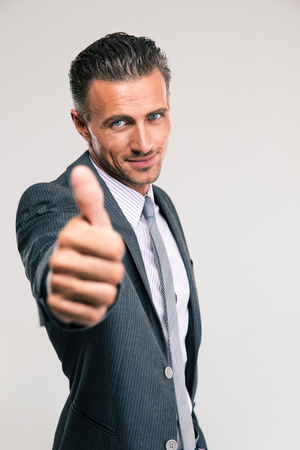 looking up: Portrait of a handsome businessman showing thumb up isolated on a white background. Looking at camera