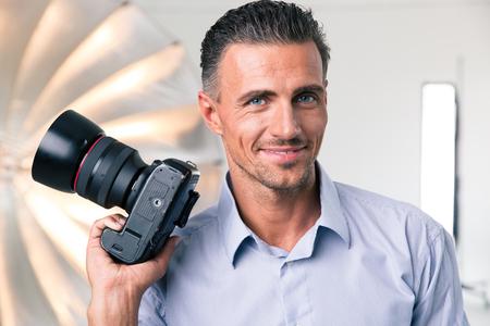 행복한 사진 작가의 초상화 스튜디오에서 카메라를 들고