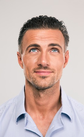 attraktiv: Glückliche durchdachte Mann auf der Suche bis auf grauem Hintergrund