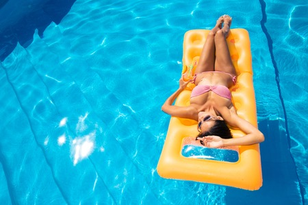 hot girl legs: Young girl resting on air mattress in the swimming pool Stock Photo