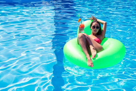 matress: Portrait of a young woman lying on air matress with cocktail in swimming pool outdoors Stock Photo