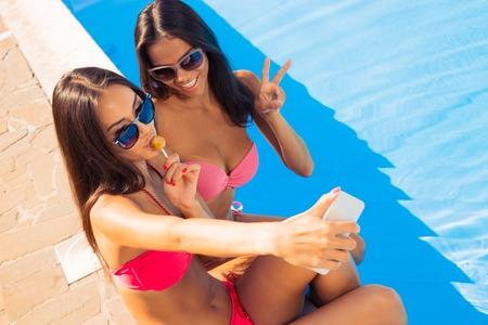 petite fille maillot de bain: Deux jolie femme en maillot de bain d�cision selfie photo sur l'ext�rieur de smartphones Banque d'images