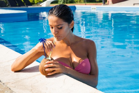 attractive young woman: Portrait of attractive young woman drinking cocktail from coconut while standing in swim pool outdoors Stock Photo