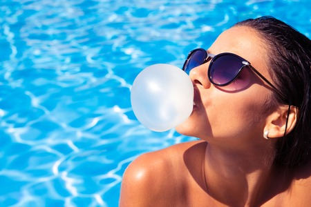 woman blowing: Charming woman in sunglasses blowing bubble with gum in swim pool outdoors Stock Photo