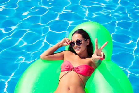 matress: Portrait of a smiling girl lying on air matress and showing victory sign in swimming pool