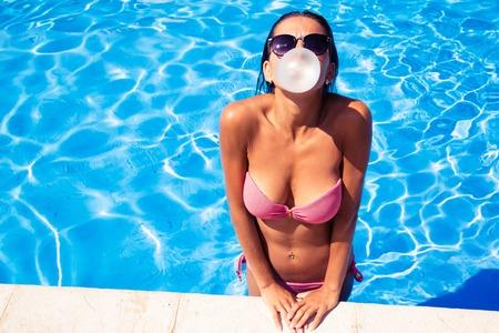 屋外プールでガムと泡を吹く美人
