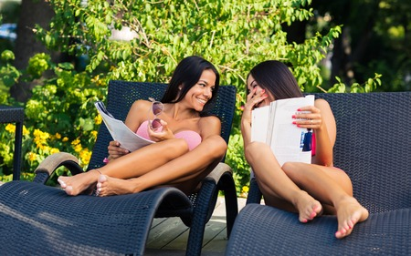 Laughing two young girls reading magazine on the deckchair outdoors Foto de archivo