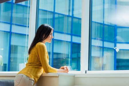 happiness or success: Portrait of a casual businesswoman looking at window in office Stock Photo