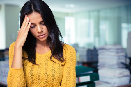 unease: Portrait of a tired casual businesswoman standing in office Stock Photo