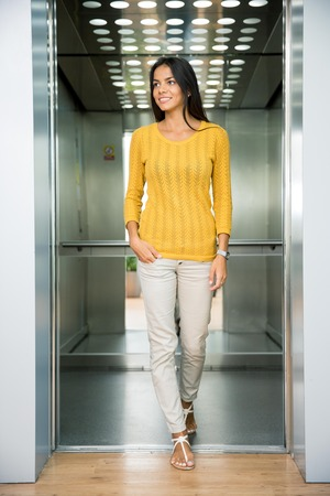 elevator: Portrait of a smiling casual businesswoman standing in elevator and looking away