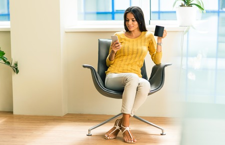 Happy businesswoman sitting on office chair with phone and cup of coffee