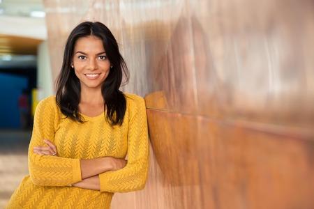 Portrét veselý atraktivní jsou potíže stojí s rukama složenýma v úřadu Reklamní fotografie