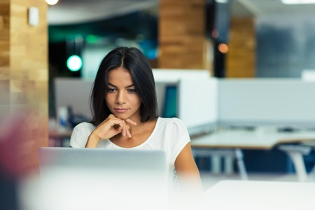 mujeres trabajando: Retrato de una empresaria seria usando la computadora port�til en la oficina Foto de archivo